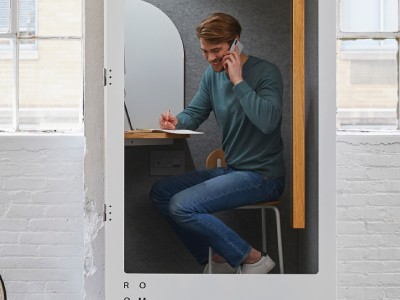 Man speaking in his phone in a work booth | Coor