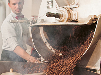 An employee roasting coffee in a coffee roasting machine | Coor