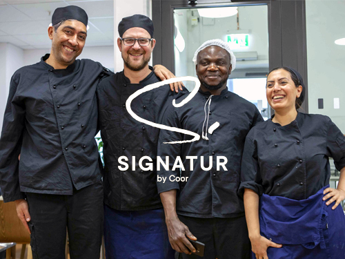 A team of four smiling chefs wearing black chef's clothes | Signatur by Coor